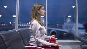 Mujer casual joven hermosa que hace la meditación de la yoga en un terminal de aeropuerto vacío contra la perspectiva de un avión metrajes