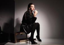 Mujer casual joven que se sienta en un taburete Imagen de archivo libre de regalías
