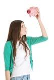 Mujer casual joven que sostiene la hucha. Fotografía de archivo