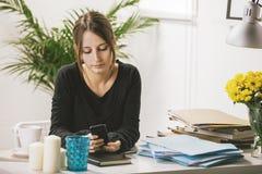 Mujer casual joven que usa smartphone en oficina. foto de archivo
