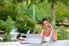 Mujer casual profesional que trabaja en línea con el ordenador portátil afuera Imágenes de archivo libres de regalías