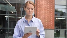 Mujer casual que camina y que usa la tableta, hojeando en línea almacen de metraje de vídeo
