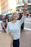 Mujer casual que graniza un taxi Imagen de archivo
