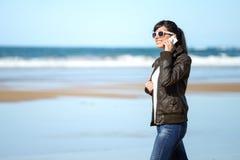 Mujer con el teléfono móvil que camina en la playa foto de archivo libre de regalías