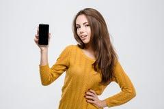 Mujer casual que muestra la pantalla en blanco del smartphone Fotos de archivo libres de regalías