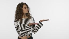 Mujer casual que presenta el espacio de la copia La muchacha hace publicidad del producto con gesto de mano metrajes