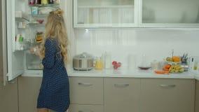 Mujer casual que saca los ingredientes alimentarios del refrigerador almacen de metraje de vídeo