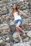 Mujer casual que se inclina en una pared enorme de la roca Foto de archivo libre de regalías