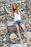 Mujer casual que se inclina en una pared enorme de la roca Fotografía de archivo