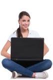 Mujer casual que se sienta con el ordenador portátil Foto de archivo libre de regalías