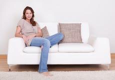 Mujer casual que se sienta en un sofá fotos de archivo