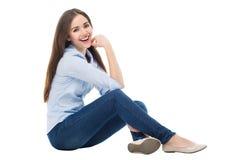 Mujer casual que se sienta sobre el fondo blanco Imágenes de archivo libres de regalías