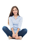 Mujer casual que se sienta sobre el fondo blanco Imagen de archivo libre de regalías