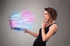 Mujer casual que sostiene el ordenador portátil con datos y numers de estallido Imagen de archivo libre de regalías