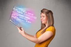Mujer casual que sostiene el ordenador portátil con datos y numers de estallido Foto de archivo libre de regalías