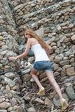Mujer casual que sube una pared enorme de la roca Fotos de archivo