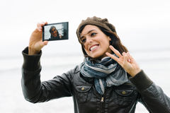 Mujer casual que toma la foto del selfie con smartphone y la sonrisa Fotos de archivo libres de regalías