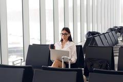 Mujer casual que trabaja en el ordenador portátil en pasillo del aeropuerto Mujer que espera su vuelo en el terminal de aeropuert fotografía de archivo libre de regalías