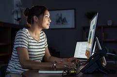 Mujer casual que trabaja tarde en el ordenador imagen de archivo libre de regalías