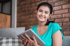 Mujer casual que usa la tableta en casa Fotografía de archivo