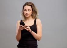 Mujer casual que usa su smartphone Fotos de archivo