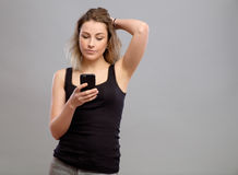 Mujer casual que usa su smartphone Foto de archivo libre de regalías