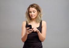 Mujer casual que usa su smartphone Foto de archivo