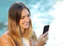 Mujer casual que usa un teléfono elegante Fotografía de archivo libre de regalías