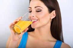 Mujer casual sana joven feliz hermosa que bebe el zumo de naranja Foto de archivo libre de regalías