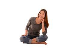 Mujer casual smilling feliz que se sienta y que piensa en el backgr blanco Imagen de archivo libre de regalías