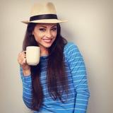 Mujer casual sonriente linda en el sombrero de paja que sostiene la taza de té y de lo Fotografía de archivo