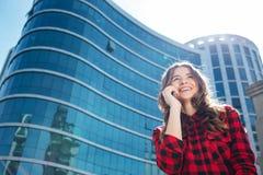 Mujer casual sonriente que habla en el teléfono al aire libre Imagen de archivo