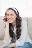 Mujer casual sonriente que se sienta en un sofá acogedor que tiene una llamada de teléfono Imagen de archivo libre de regalías