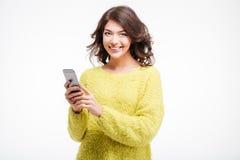 Mujer casual sonriente que sostiene smartphone Fotos de archivo libres de regalías