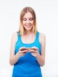 Mujer casual sonriente que usa smartphone Imágenes de archivo libres de regalías