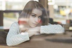 Mujer caucásica adolescente joven hermosa en el suéter que se sienta en el th Foto de archivo libre de regalías