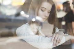 Mujer caucásica adolescente joven hermosa en el suéter que se sienta en el th Imagen de archivo