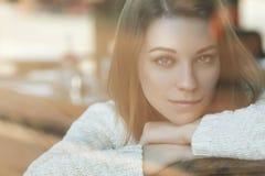 Mujer caucásica adolescente joven hermosa en el suéter que se sienta en el th Imagenes de archivo
