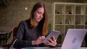 Mujer caucásica atractiva del jengibre que charla usando la tableta y que sonríe en el fondo de la oficina almacen de video