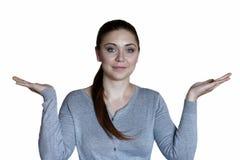 Mujer caucásica atractiva joven con los ojos azules y para arriba aumentados los brazos de las palmas en usted que ofrece algo foto de archivo libre de regalías