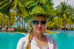 Mujer caucásica atractiva joven en sombrero divertido en la playa tropical fotos de archivo
