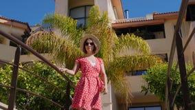 Mujer caucásica atractiva joven que lleva el vestido, el sombrero rojo y las gafas de sol mirando el sol con las palmeras en el f almacen de metraje de vídeo
