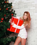 Mujer caucásica atractiva rubia con el regalo rojo cerca de la Navidad Fotografía de archivo libre de regalías