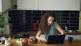 Mujer caucásica bastante positiva rizada joven que trabaja en el ordenador portátil y que habla en el teléfono que se sienta en c almacen de metraje de vídeo