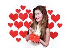 Mujer caucásica blanca con los labios rojos que sostienen un regalo en una mano y fondo en forma de corazón sonriente Concepto de Foto de archivo libre de regalías