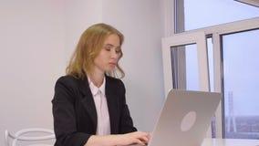 Mujer caucásica blanca elegante hermosa que se sienta en la oficina y que trabaja en su ordenador portátil almacen de metraje de vídeo