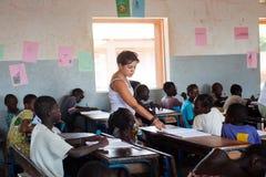 Mujer caucásica blanca que enseña a niños negros en África fotografía de archivo