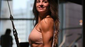 Mujer caucásica bonita de la aptitud que bombea para arriba ejercicios del ABS del fondo del gimnasio del concepto de la aptitud  almacen de video