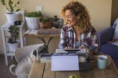 Mujer caucásica bonita de la Edad Media utilizar una máquina de escribir vieja para escribir un blog o un libro al aire libre cer imagen de archivo