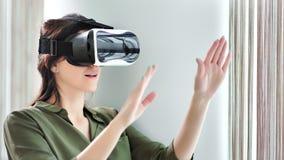 Mujer caucásica confiada que usa la tecnología moderna de la visión del dispositivo del vr que sumerge en el ciberespacio almacen de metraje de vídeo